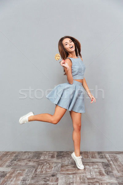 Cheerful carefree young woman with lollipop running and jumping Stock photo © deandrobot