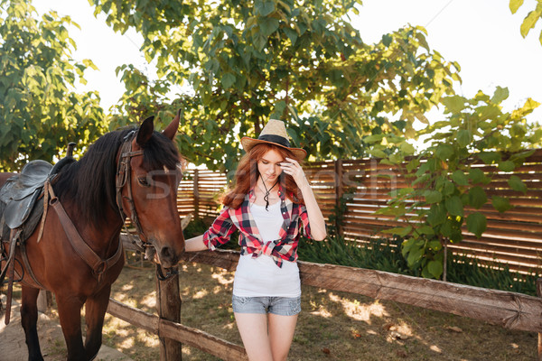 Woman cowgirl walking with her horse in village Stock photo © deandrobot