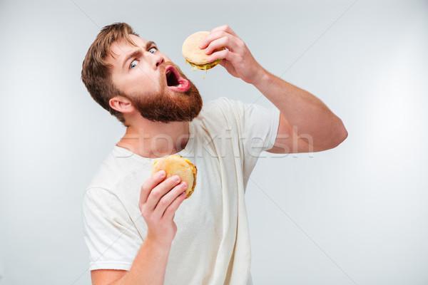 Excité barbu homme manger isolé Photo stock © deandrobot