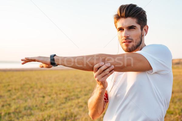 Koncentrált sportoló nyújtás kezek zenét hallgat fülhallgató Stock fotó © deandrobot