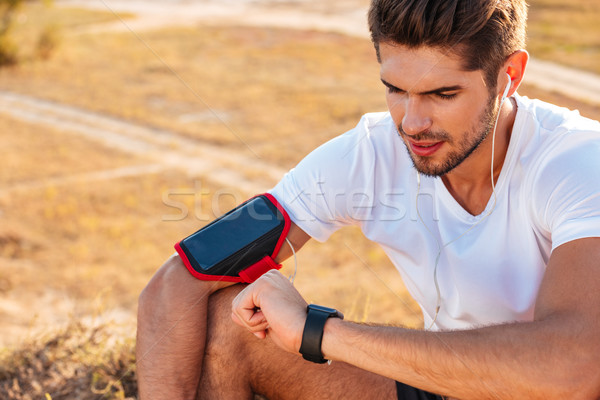 Concentrated young sportsman sitting and using smart watch Stock photo © deandrobot