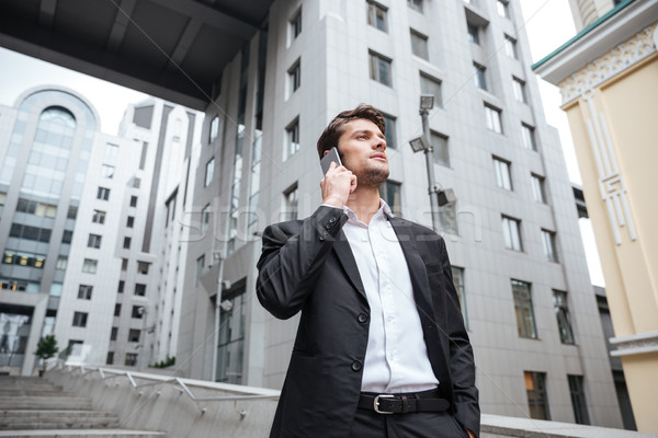 Serious young businessman talking on cell phone near business center Stock photo © deandrobot