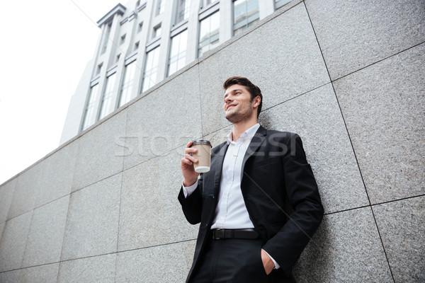 Cheerful young businesman drinking coffee outdoors Stock photo © deandrobot