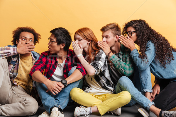 Multiethnic group of young people telling secrets to each other Stock photo © deandrobot