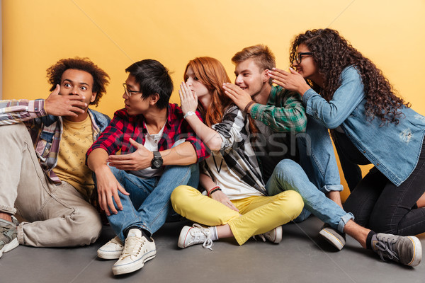 Group of people surprising and telling secrets to each other Stock photo © deandrobot