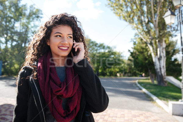Attractive dark-skinned young woman talking at phone Stock photo © deandrobot