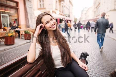 улыбающаяся женщина сидят говорить мобильного телефона скамейке улыбаясь Сток-фото © deandrobot