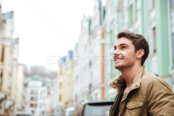 Joyful young man walking on the street and looking aside. Stock photo © deandrobot