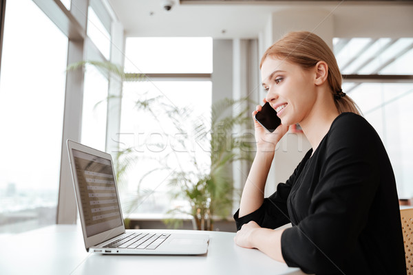 Woman worker using laptop computer and talking by phone Stock photo © deandrobot