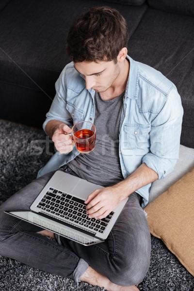 Człowiek pitnej herbaty wpisując laptop górę Zdjęcia stock © deandrobot