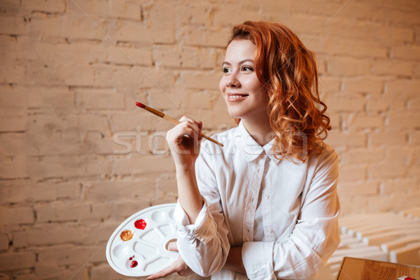 Happy young redhead woman painter Stock photo © deandrobot