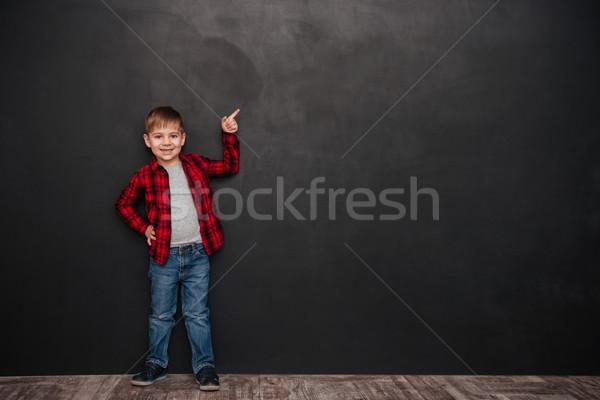 Sevimli küçük erkek ayakta kara tahta işaret Stok fotoğraf © deandrobot