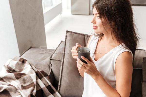 Békés nő ül kanapé iszik kávé Stock fotó © deandrobot
