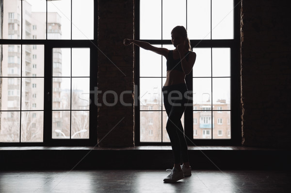 Silhouette of woman athlete standing and doing shadow boxing exercises Stock photo © deandrobot