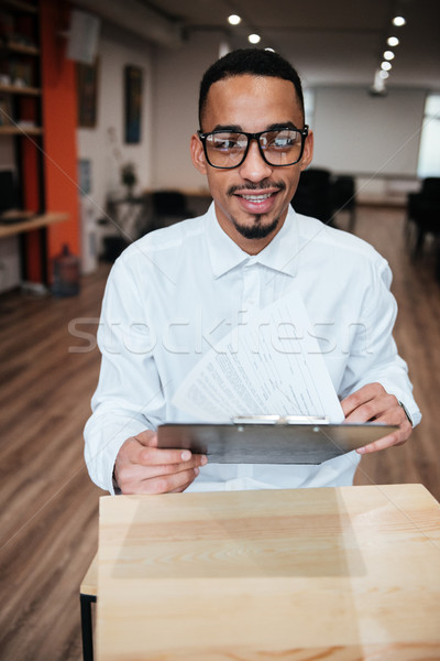 Attractive african businessman looking at notepad. Coworking. Stock photo © deandrobot