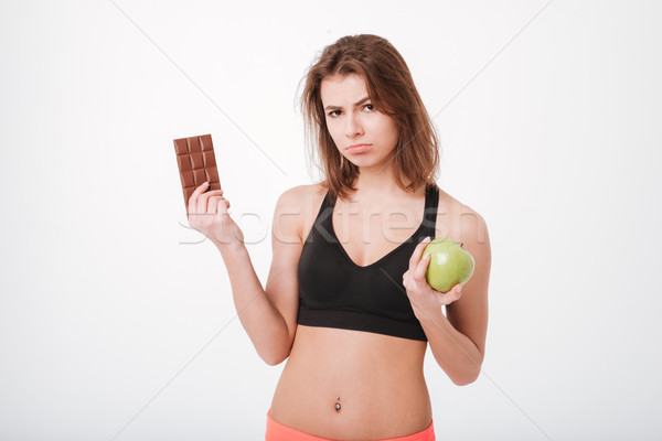 Sad young fitness lady holding apple and chocolate Stock photo © deandrobot