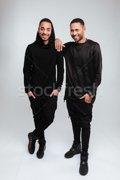 Two cheerful african american young men standing and laughing Stock photo © deandrobot