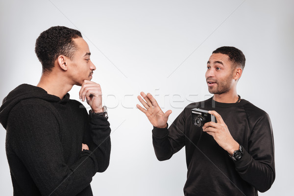 Stock photo: Young african men standing over white background with camera