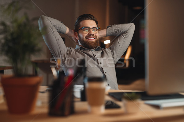 Happy bearded designer working at night and stretching. Stock photo © deandrobot