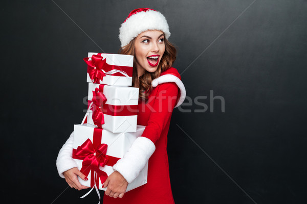 Cheerful woman in red santa claus outfit holding xmas presents Stock photo © deandrobot