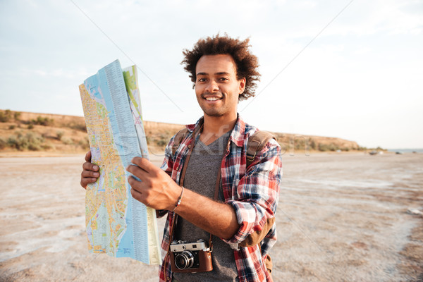 Happy man tourist with backpack standing and holding map outdoors Stock photo © deandrobot