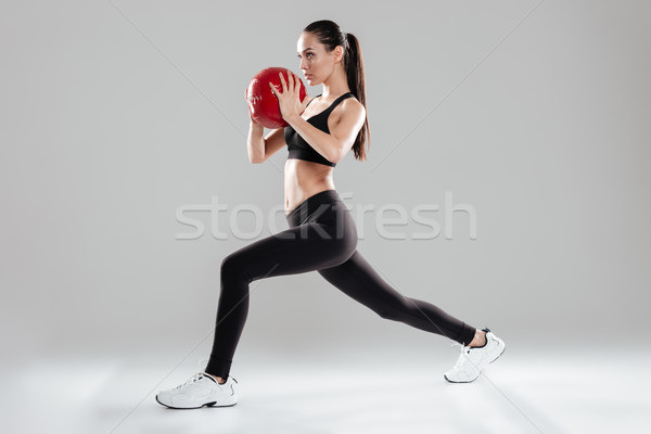 Focused beautiful young sportswoman doing exercises with medicine ball Stock photo © deandrobot