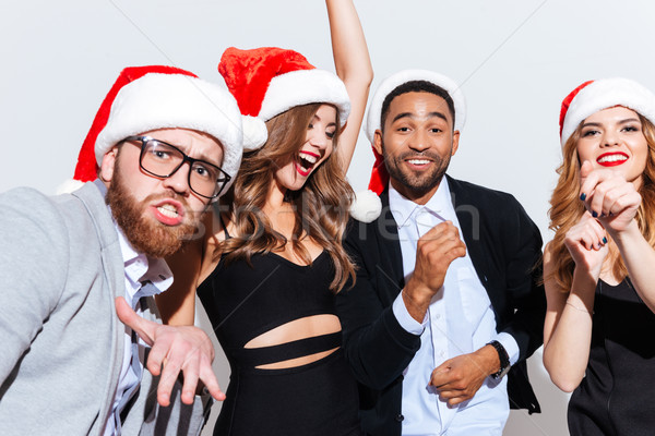 Smiling young people in santa claus hats having fun together Stock photo © deandrobot