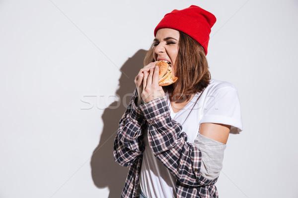 Aç genç kadın yeme Burger fotoğraf gömlek Stok fotoğraf © deandrobot