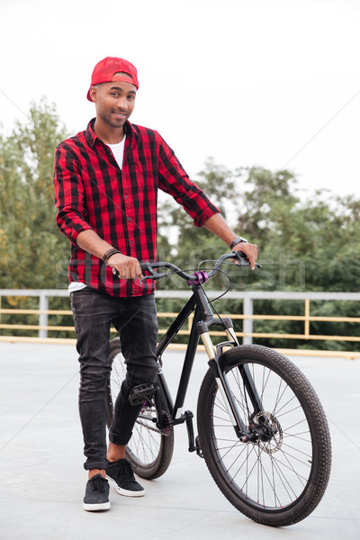 Happy dark skinned guy standing near his bicycle Stock photo © deandrobot