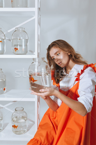 Stock photo: Attractive woman holding and looking at gold fish in jar
