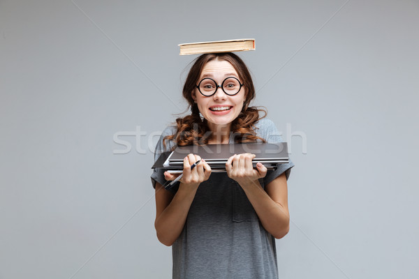 Surprised Happy Female nerd with book on head Stock photo © deandrobot