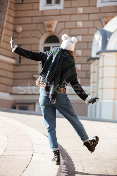 Back view of woman walking in city and having fun Stock photo © deandrobot