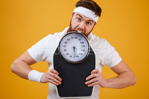 Portrait of a angry sports man biting weight scales Stock photo © deandrobot