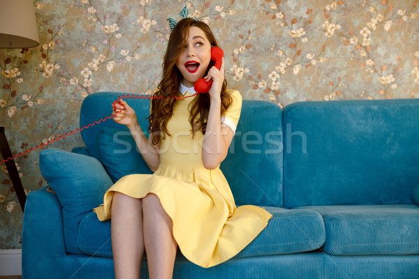 Amazing young pin-up lady talking by phone. Stock photo © deandrobot