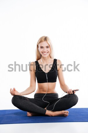 Cheerful fitness woman sitting make yoga exercises Stock photo © deandrobot