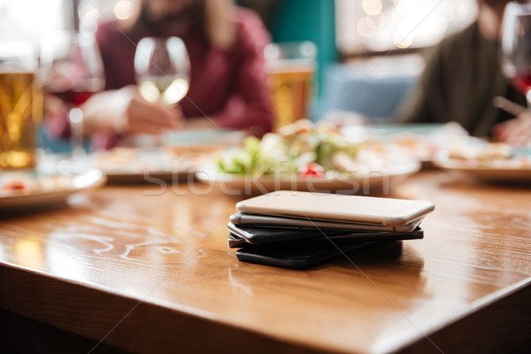 Stock photo: Friends in cafe. Focus on mobile phones on table.