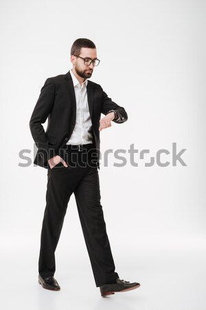 Bearded businessman looking at watch. Stock photo © deandrobot