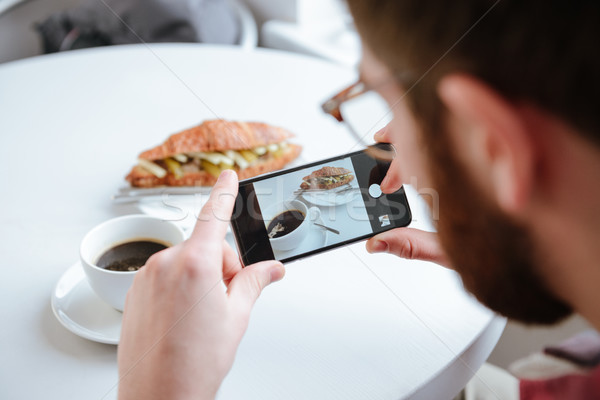 Side view of a man taking photo of his food in cafe Stock photo © deandrobot