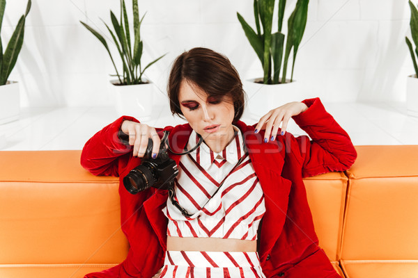 Attractive young woman photographer holding modern photo camera Stock photo © deandrobot