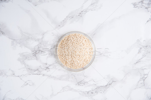 Top view of white sesame in a bowl isolated on white Stock photo © deandrobot