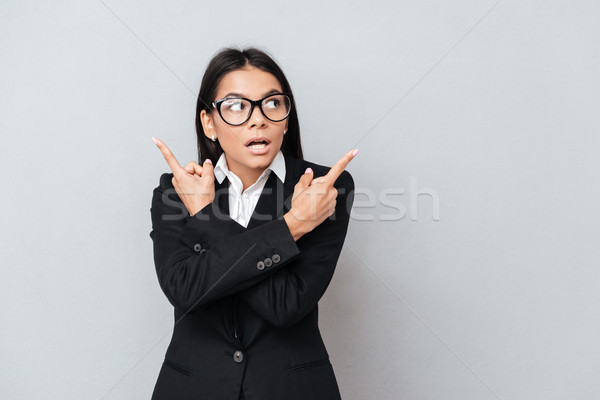 Young astonished business woman pointing sideways with two hands Stock photo © deandrobot