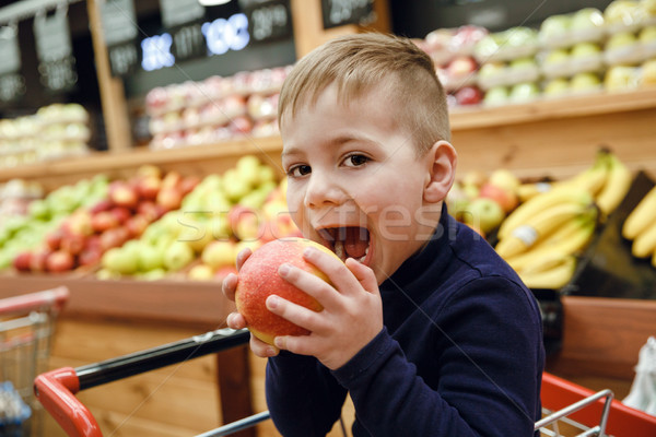 Side view of young boy biting apple Stock photo © deandrobot