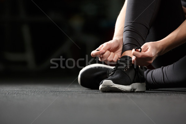 Cropped image of young fitness lady tie laces in gym. Stock photo © deandrobot