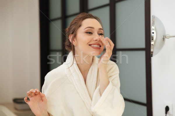 Stock photo: Cheerful young woman standing and touching her face in bathroom