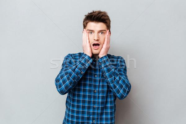 Jonge man geschokt verrassend camera jonge knappe man Stockfoto © deandrobot