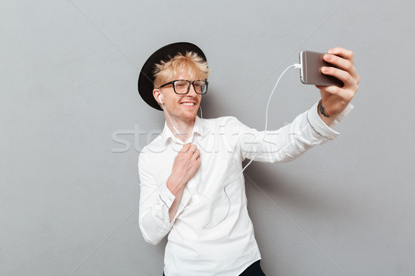 Stock photo: Man wearing glasses listening music while make selfie.