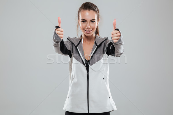 Smiling female runner in warm clothes showing thumbs up Stock photo © deandrobot