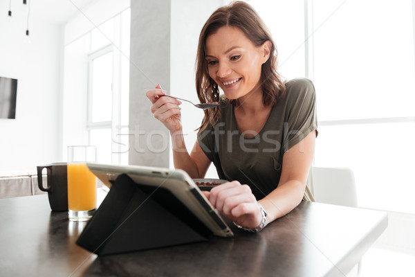 Happy casual woman eating by the table on kitchen Stock photo © deandrobot