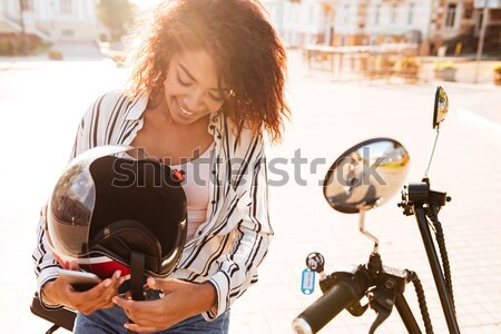 Smiling curly woman in sunglasses rides on modern motorbike Stock photo © deandrobot
