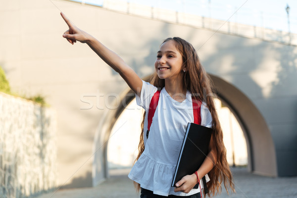 Smiling brunette schoolgirl posing outdoors pointing and looking away Stock photo © deandrobot